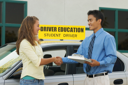 A driving instructor congratulates his student on passing her road test first time.
