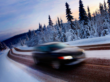 A car driving along a highway in the cold, slipper winter when the sun is setting.