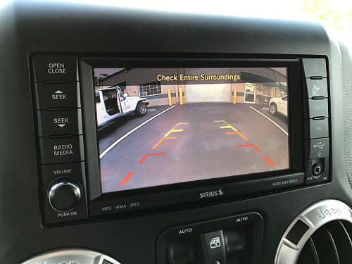 You can use a backup camera for your driver's test. Check it as you would your mirrors, however, you'll still be looking out the rear window for the duration of the back.