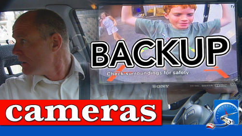 A backup camera can be used for a driver's test, but NOT as your primary line of sight. You must look out the rear window for the duration of the backup.